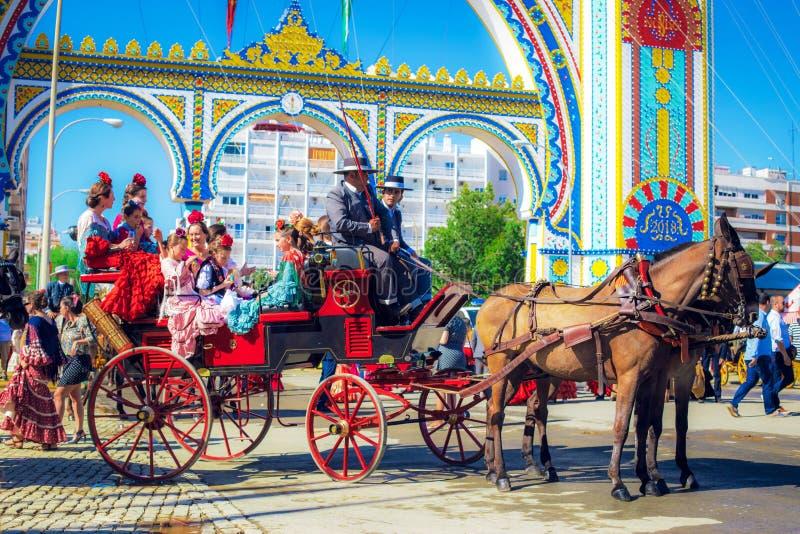 Familles espagnoles dans la robe traditionnelle et colorée voyageant dans chariots hippomobiles chez April Fair, foire de Séville photographie stock libre de droits
