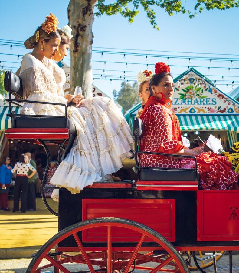 Familles espagnoles dans la robe traditionnelle voyageant dans chariots hippomobiles chez April Fair, Séville Feria de Sevilla ju photo stock