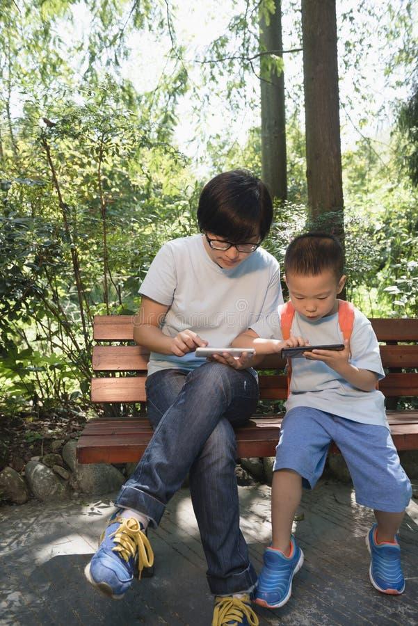 Familles jouant le smartphone photos libres de droits