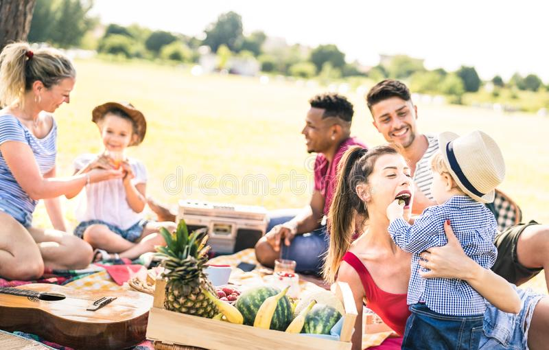 Familles multiraciales heureuses ayant l'amusement avec des enfants à la partie de barbecue de pique-nique - bonheur multiculture photos libres de droits