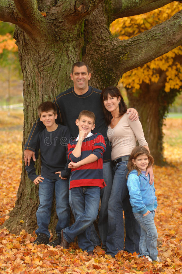 Family. A close family poses amid yellow fallen leaves and old maples