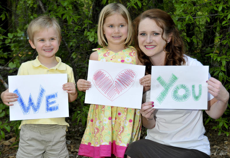 Family. A single mom and her son and daughter holding signs stock photo