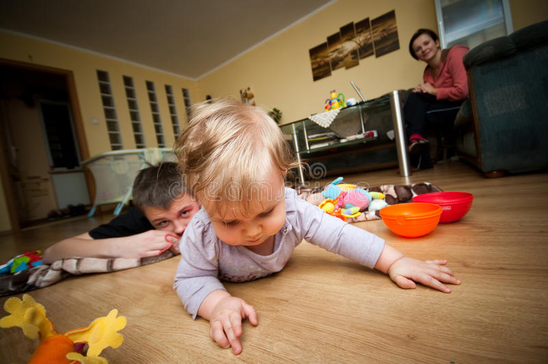 Family. At home scene - baby girl crawls on the floor, brother and mother in the background stock photos