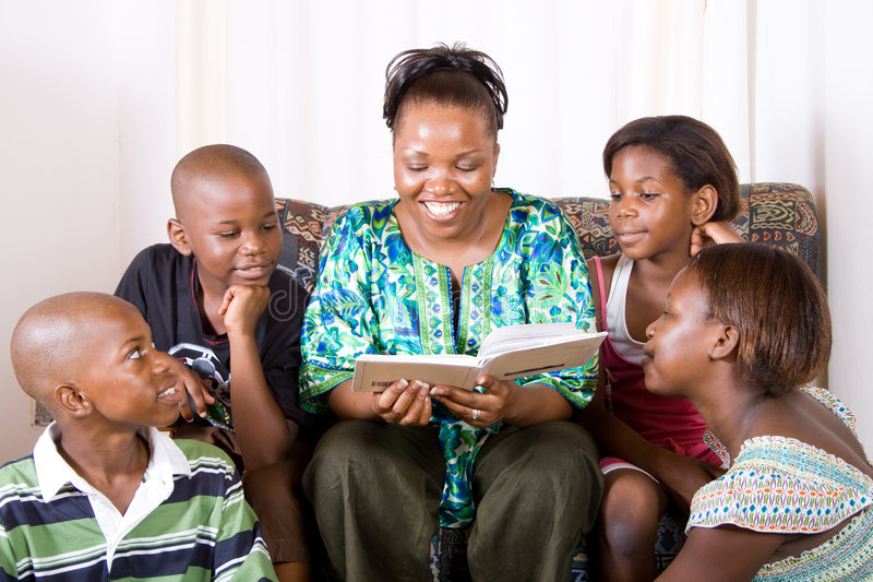 Family. A happy family - african mother reading a book to her 4 children in living room