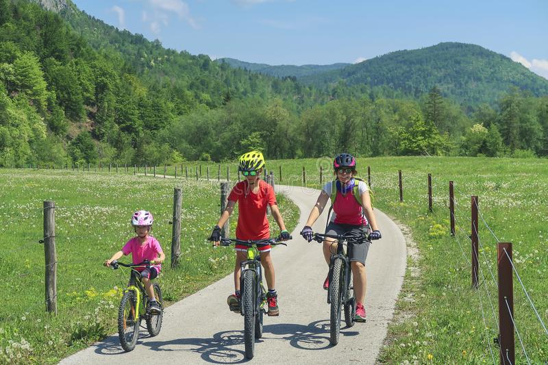 Family active vacation. Green destination. Cycling in the national park. Active lifestyle, healthy lifestyle. Family by the lake, mountains in the background stock photo