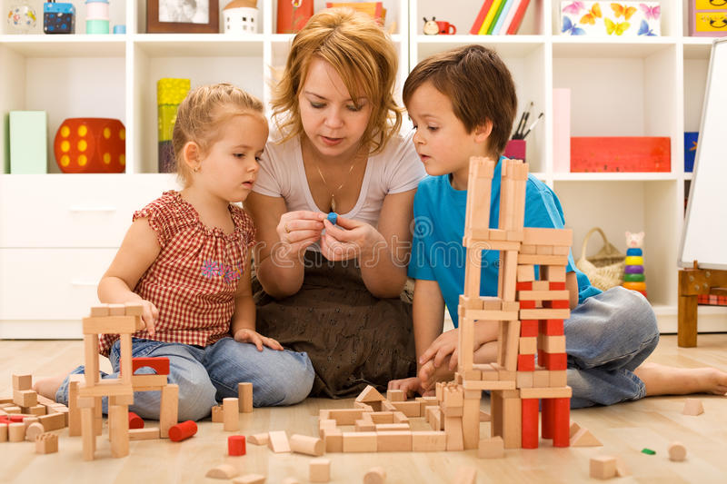Family activities in the kids room. Woman and children sitting on the foor playing royalty free stock images