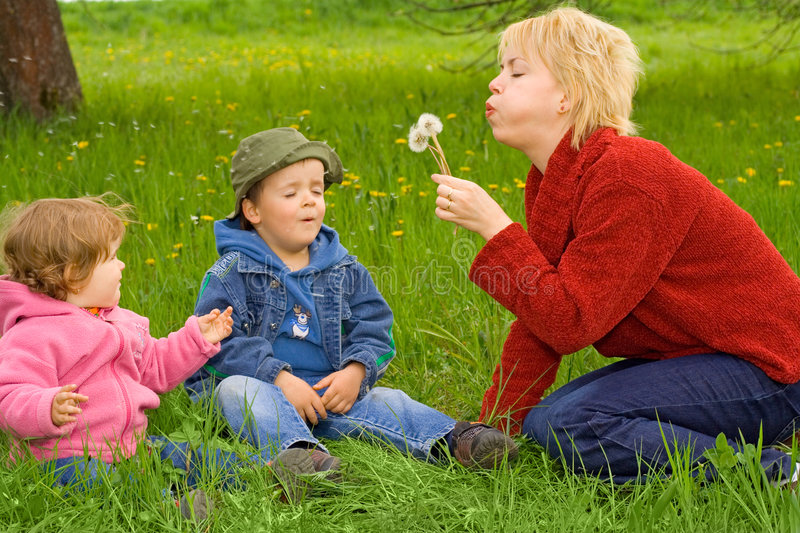 Family activities outdoors. Young mother with little boy and girl blowing dandelions sitting in the grass stock image