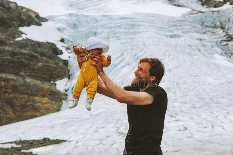 Family adventure father holding up baby climbing in glacier mountains stock photos