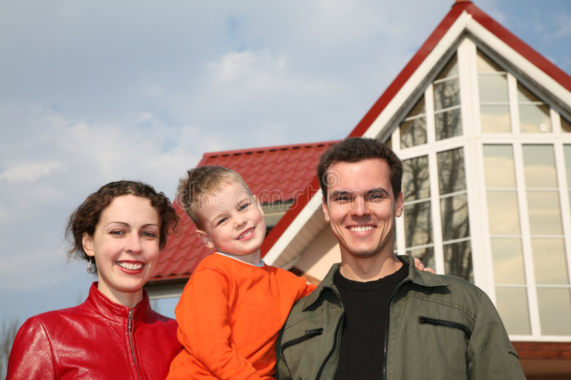 Family against new house. Smiley family and new house