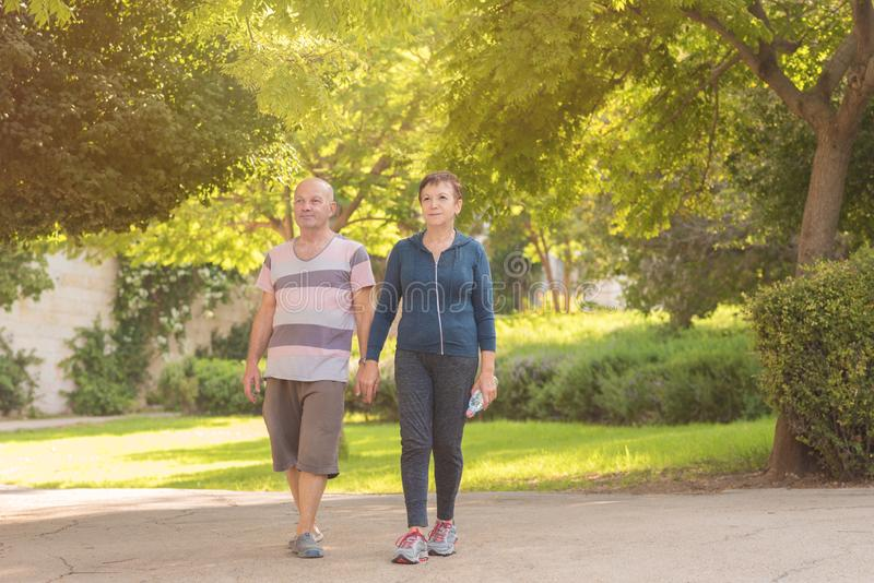 Family, age, sport, healthy and people concept - happy senior couple holding hands and exercising together. royalty free stock image