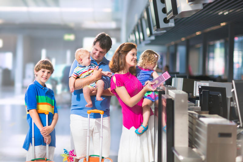 Family at the airport. Big happy family with three kids travelling by airplane at Dusseldorf International airport, parents with teenager boy, toddler girl and