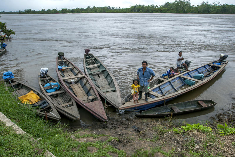 A family in the Amazon River town of Indiana in Peru. A man and his family aboard a boat in Indiana, a town on the Amazon River in Peru. The Amazon River rose stock images