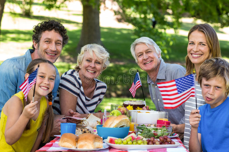 Family with American flag having a picnic. In a park royalty free stock images