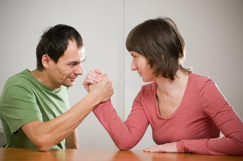 Family arm wrestling. A family comic arm wrestling stock image