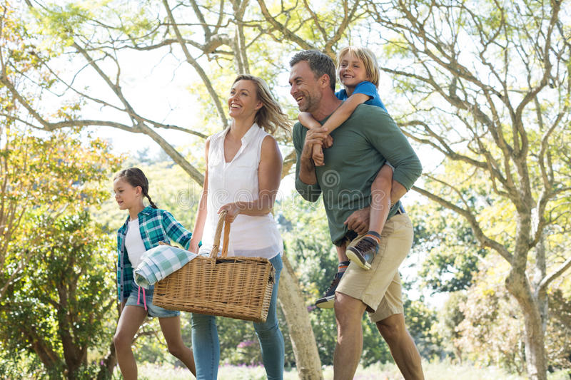 Family arriving in the park for picnic on a sunny day royalty free stock photo