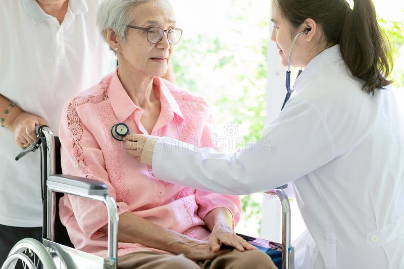 Family asian doctor or smiling nurse checking,listening senior patient's chest through stethoscope during home visit,young royalty free stock images