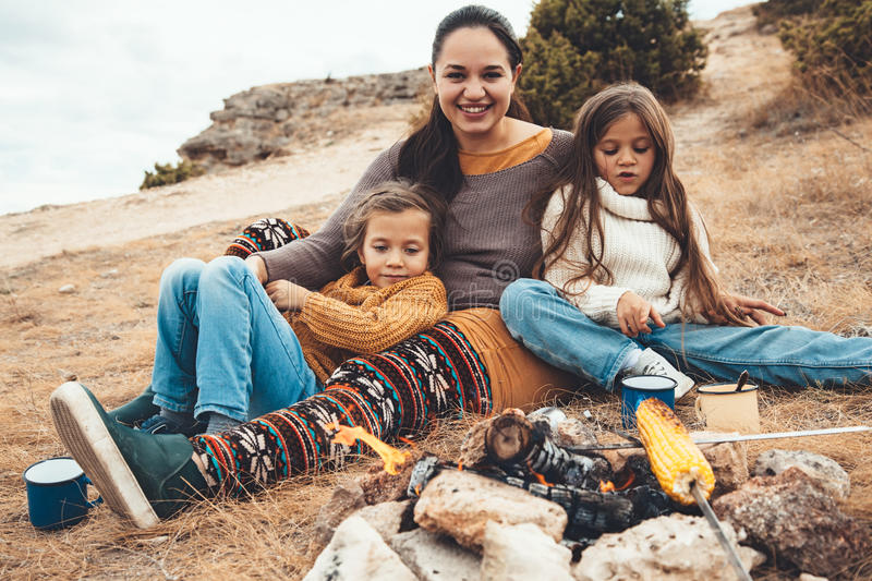 Family in autumn hike. Family sitting by the fire and frying sausages in field. Autumn hike in cold weather. Warming and cooking near flame together royalty free stock photos