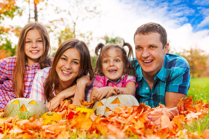 Family in autumn leaves with Halloween pumkins royalty free stock photo