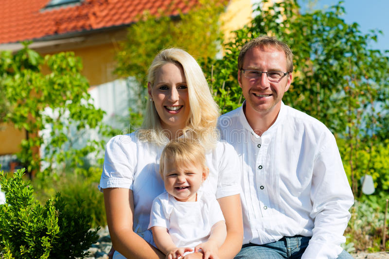 Family with baby child in front of house royalty free stock photography