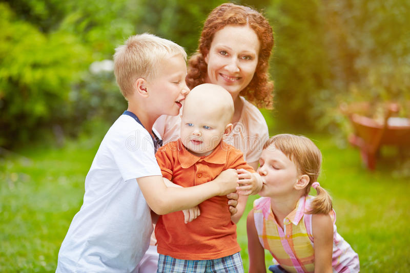 Family with baby and children in garden. Family with baby and two children together in a garden in summer stock photo