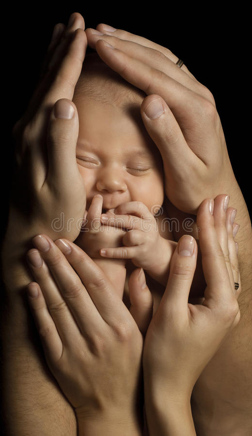Family and Baby. New Born Kid in Parents Hands. Child Birth and Care Concept. Newborn Sleeping. On Black Background stock photos