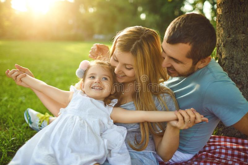 Family with baby sitting on grass in the park. Family with baby sitting on green grass in the park with sunlight in summer. The concept of a happy family stock photo