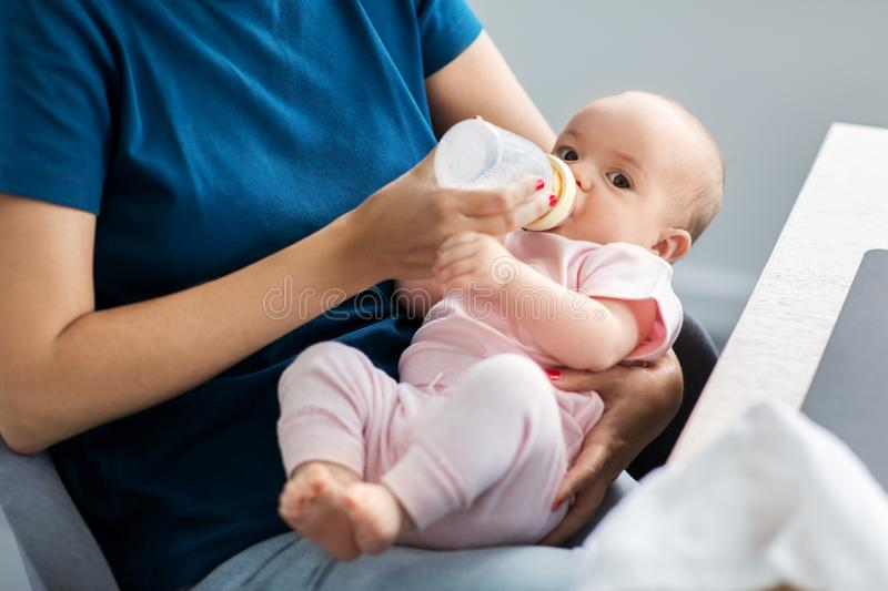 Close up of mother feeding baby with milk formula stock image