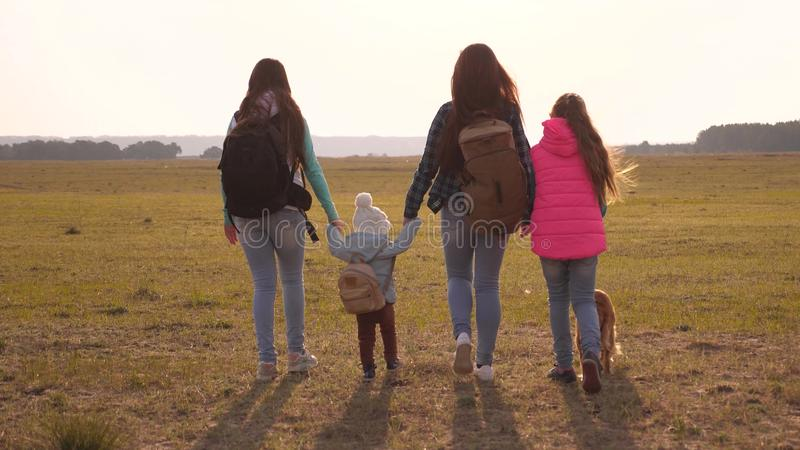 Family with backpacks travels with a dog. teamwork of a close-knit family. mother, daughters and home pets tourists. The concept of a sports family holiday in royalty free stock photography