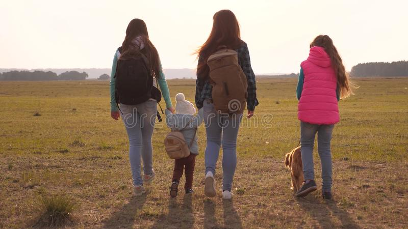 Family with backpacks travels with a dog. teamwork of a close-knit family. mother, daughters and home pets tourists stock image