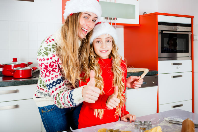 Family baking Christmas cookies in kitchen. Mother and daughter baking X-mas cookies at home in domestic kitchen stock photo