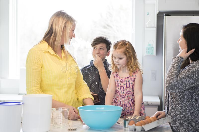 Family baking together in a modern kitchen. Mom and kids having fun baking in the kitchen. Teens and toddler and a single mom stock photography