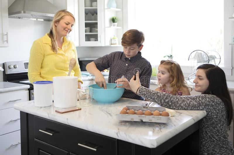 A family baking together in their modern kitchen. A family baking together as the daughter takes a selfie.Their kitchen is bright and modern stock photo