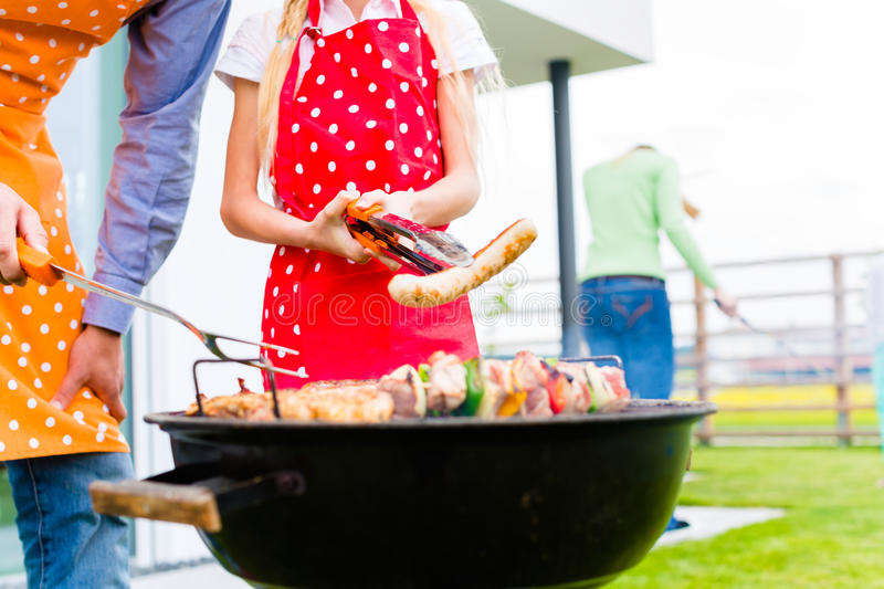 Family barbecue together in garden home royalty free stock images