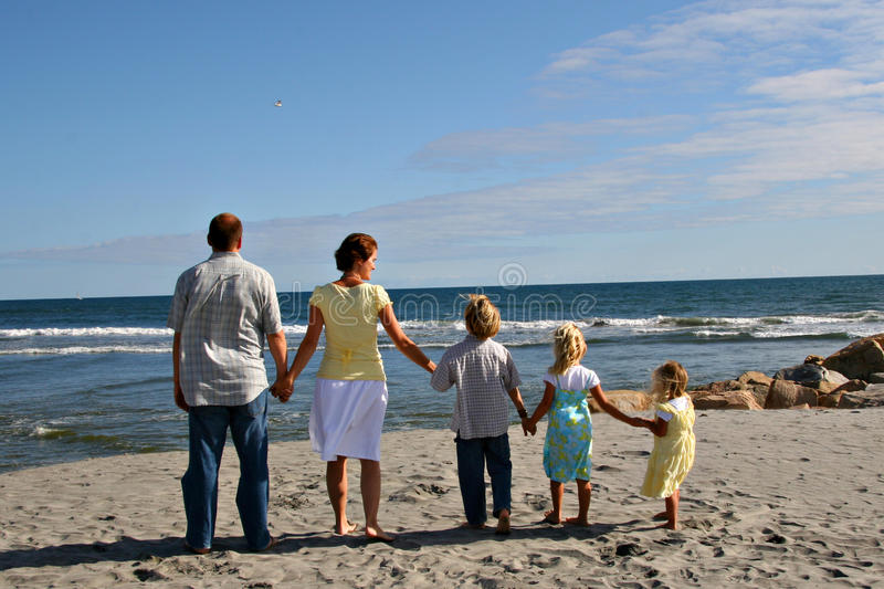 Family on the Beach. A happy family of 5 on the beach holding hands