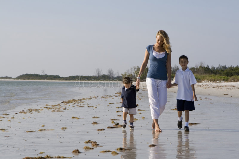Family on a beach. Mom with kids walking on a beach. Sky and ocean in the background royalty free stock photo