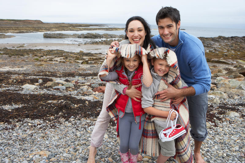 Family on beach with blankets. Smiling at camera royalty free stock image