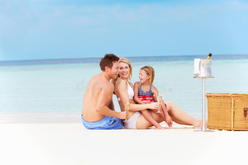 Family On Beach With Luxury Champagne Picnic. Smiling stock photo