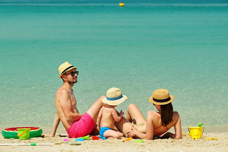 Family on beach. Toddler playing with mother and father. royalty free stock photography