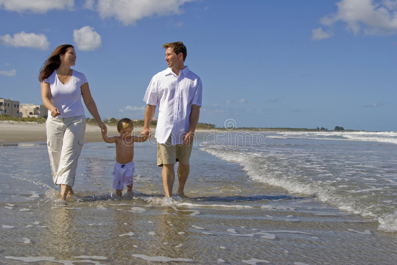 Family beach walk. Young family walking on a beach royalty free stock photography