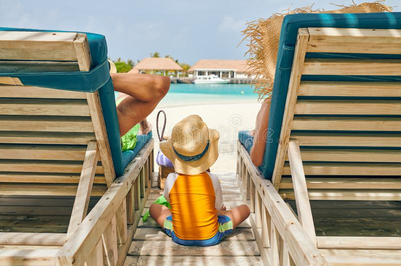 Family at beach on wooden sun bed loungers. Young couple with three year old boy. Summer vacation at Maldives royalty free stock photo