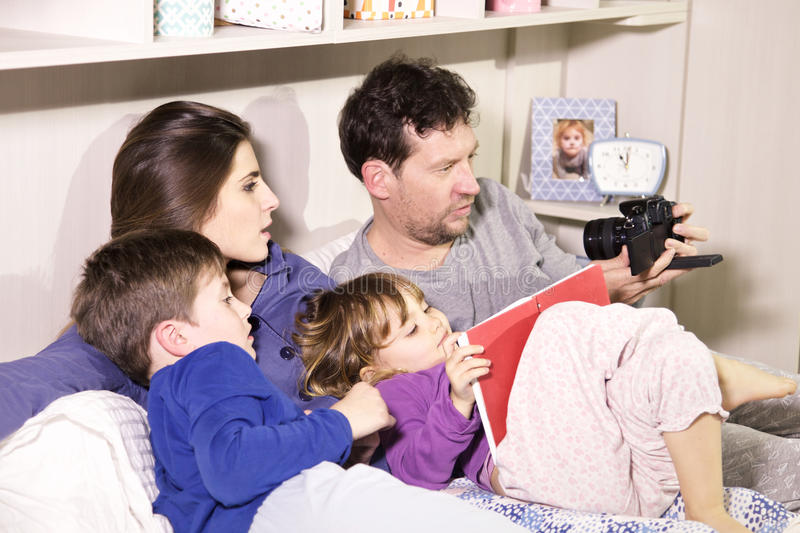 Family in bed taking selfie with camera royalty free stock photo
