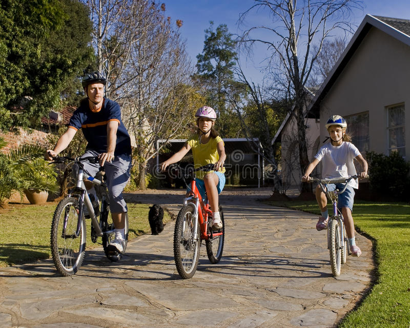Family Bicycle Ride. Dad and his two daughters go for an afternoon ride on their bikes