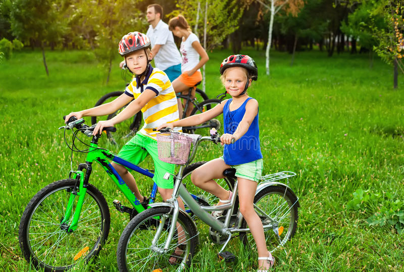 Family on bicycles on the grass field royalty free stock photo