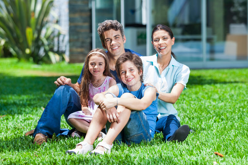 Family in big house. Happy family sitting on grass in front of house, parents with two children smile