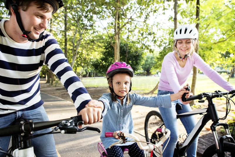 Family on a bike ride in the park royalty free stock images