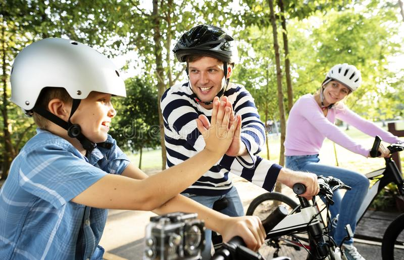 Family on a bike ride in the park royalty free stock image