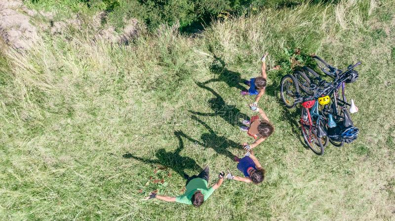 Family on bikes cycling outdoors, active parents and kids on bicycles, aerial top view of happy family with children near river royalty free stock photo