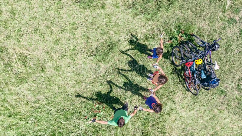 Family on bikes cycling outdoors, active parents and kids on bicycles, aerial top view of happy family with children stock photo
