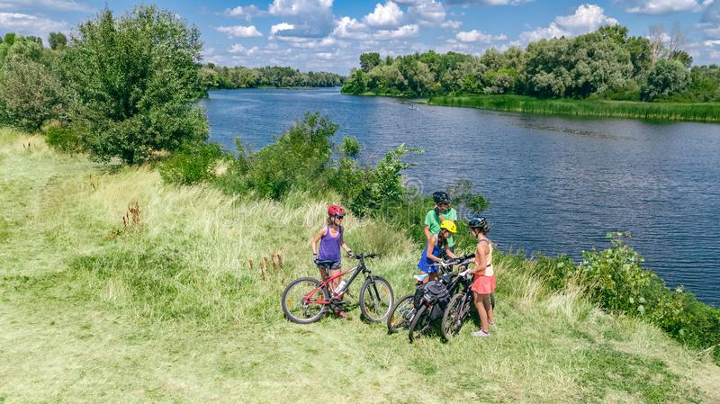 Family on bikes cycling outdoors, active parents and kids on bicycles, aerial top view of happy family with children near river royalty free stock photography