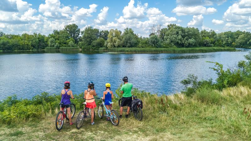 Family on bikes cycling outdoors, active parents and kids on bicycles, aerial view of happy family with children relaxing. Near beautiful river from above stock photo